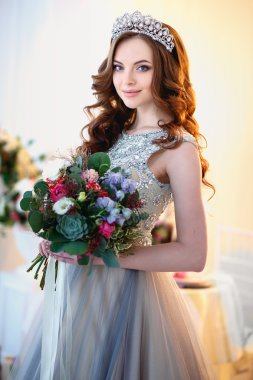 Beautiful young lady in a luxury dress in elegant interior with a bouquet of flowers