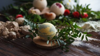 Preparation of bath bombs. Ingredients and floral decor on a wooden vintage table.