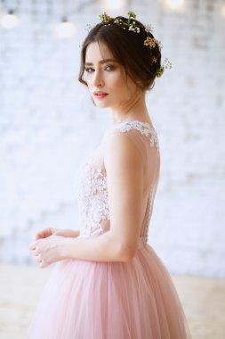 Bride in a tender light pink wedding dress in a morning. Fashion beauty portrait