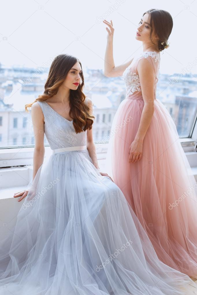 Two brides in a tender light pink