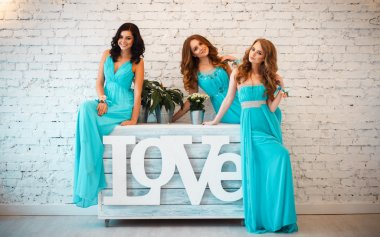 Three beautiful bridesmaids in similar blue dresses with perfect make up and hair style in a light loft space