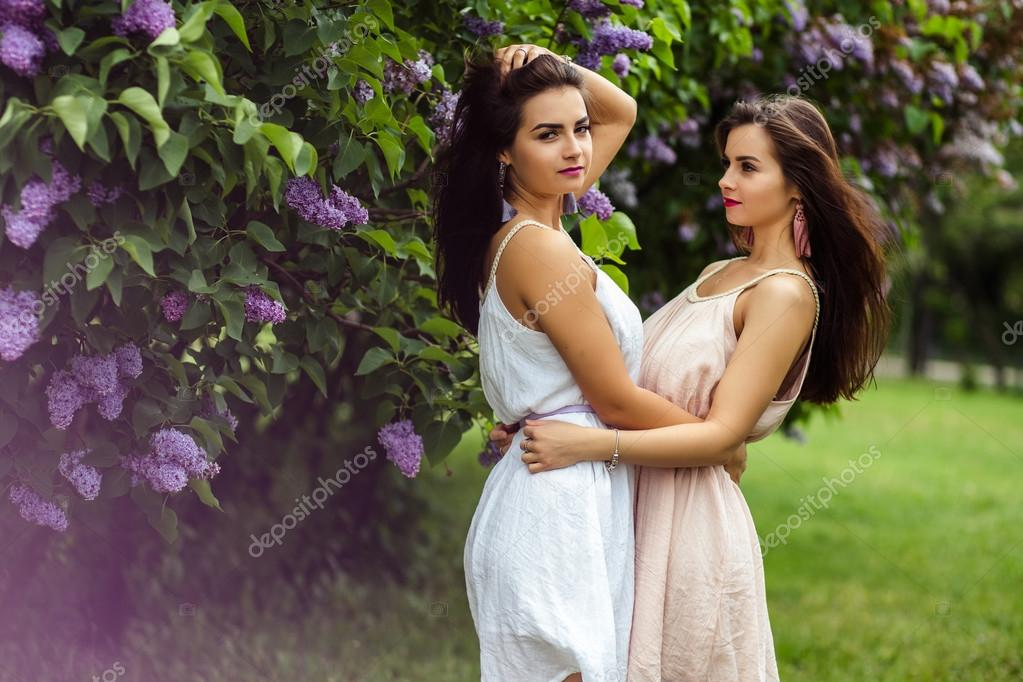 94ab1423455 Two beautiful twins young women in summer dresses near blooming lilac —  Stock Photo