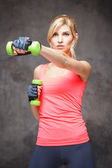 Schöne blonde junge Frau im Sport Stil