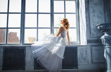 Beautiful blonde bride with perfect makeup and hair style in elegant interior