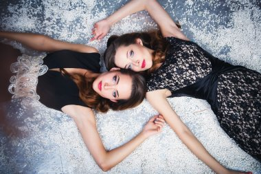 Portrait of beautiful twins young women in gorgeous evening dresses