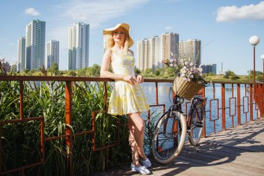 Beautiful sweet blonde woman walks with bicycle near skyscrapers