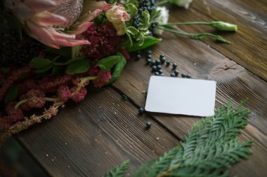 Florist workplace: visit card and flowers and accessories on a vintage wooden table. soft focus