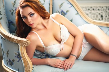 Beautiful sexy redhead young woman in lingerie lying on blue sofa