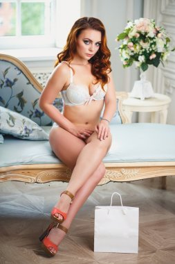 Beautiful sexy redhead young woman in lingerie lying on blue sofa with white bag package