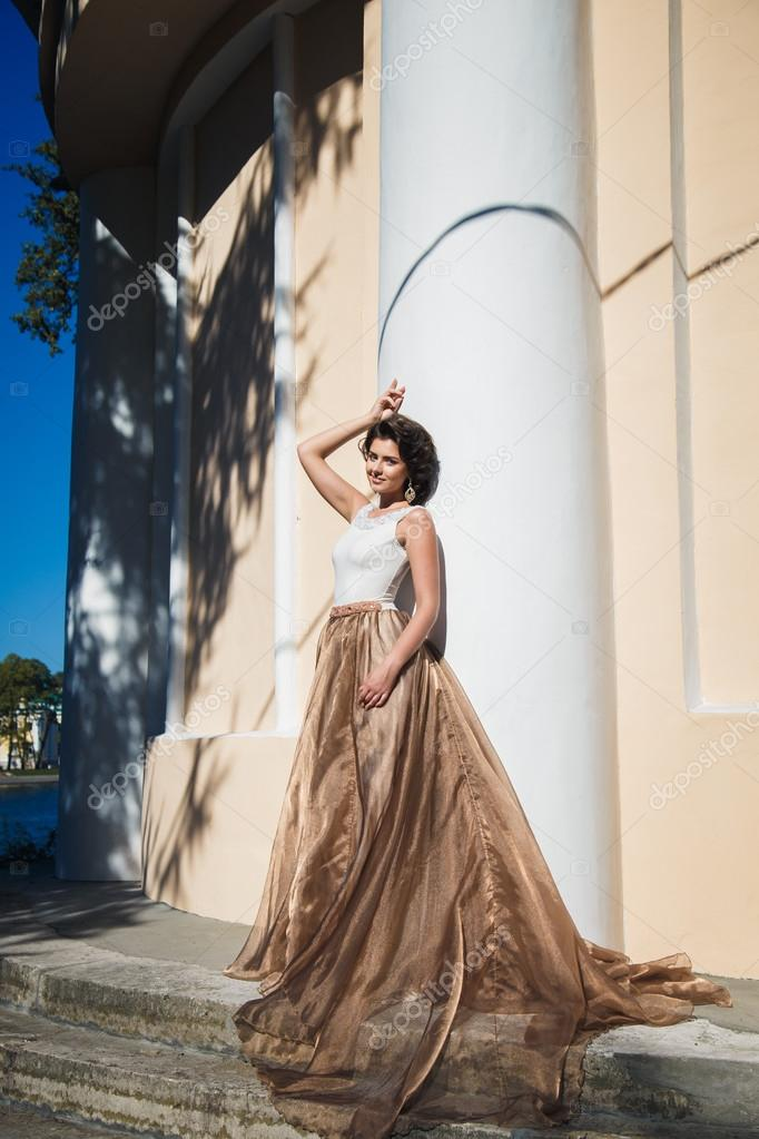67e772274e1 Портрет красивой элегантный невеста в великолепные Бежевое платье гуляет в  парке– Стоковое изображение