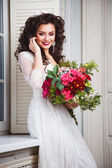 Close-up portrait of gorgeous beautiful bride in white dress with amazing hair style and make up, holding bouquet