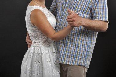 Unrecognized caucasian middle aged couple dancing against black