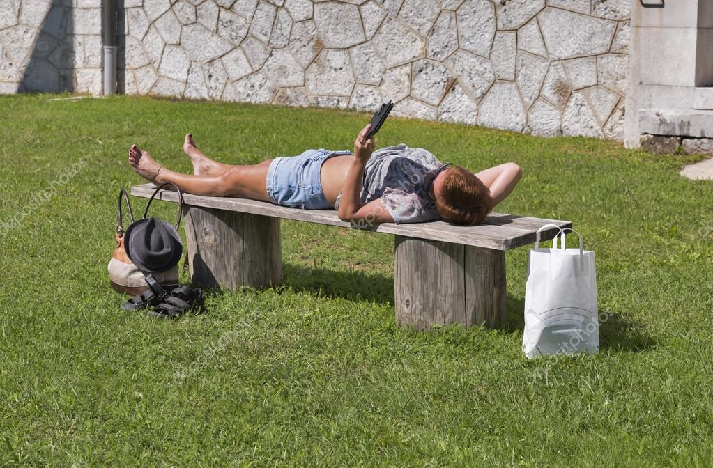 tanned woman lying on a bench and reading electronic book