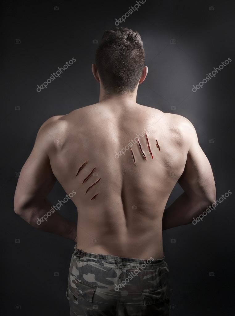 Sexy Male Body with Scratches from nails on his Back. Handsome Muscular Man  with Athletic Body Topless on a dark background. Passionate Lover.