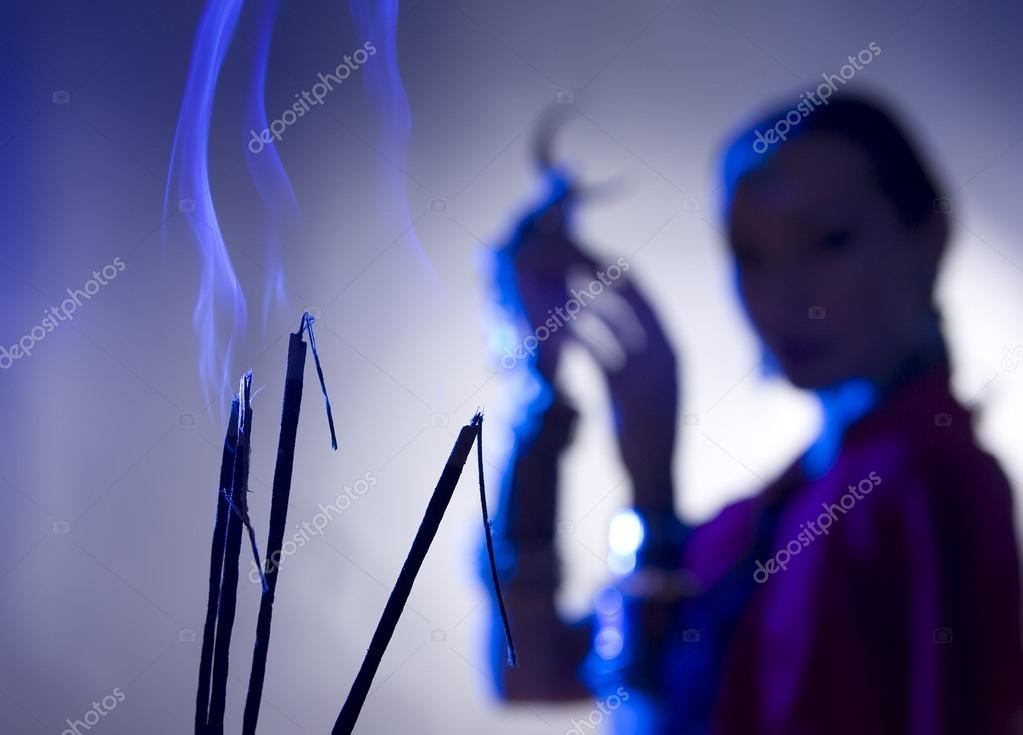 Beautiful indian woman silhouette with incense holding a moon sy