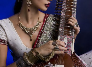 Beautiful Indian Woman in Sari with Oriental Jewelry Playing the