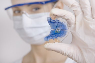Dentist holding Retainer for Teeth, Close-up