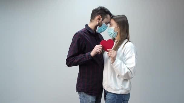 Mladý pár v ochranných lékařských maskách se dotkl jejich hlav, červené papírové srdce drželi v rukou.