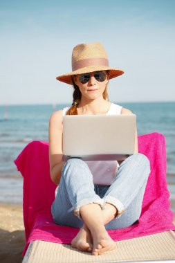 Full length portrait of casual businesswoman working by the sea on summer holiday. Middle aged female sitting on  sunbed by the seaside and typing on her laptop. stock vector