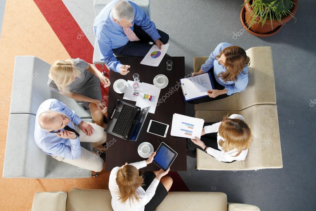 Mensen uit het bedrijfsleven zitten rond bureau u stockfoto sepy