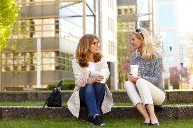 two mature businesswomen drinking coffee