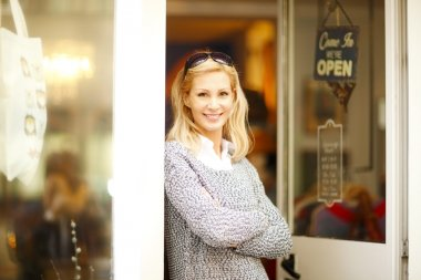 confident female owner at shop facade