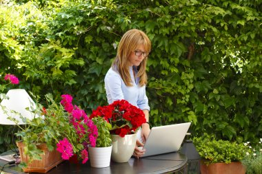 woman working with laptop at flower shop