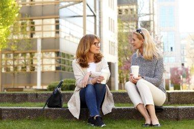 women sitting at park on coffee break