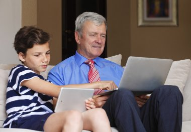 Teenager teaching  grandfather