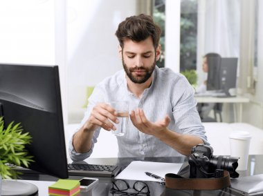 Portrait of young businessman takes the pill with a glass of water while sitting at office desk in front of computer. stock vector
