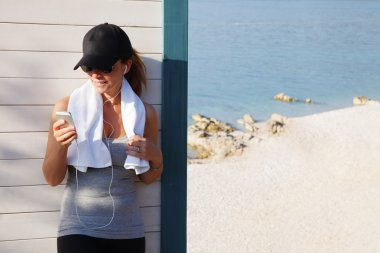 fit female standing at seaside after running