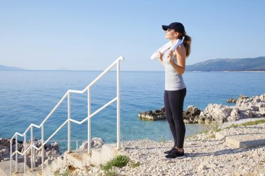 Fit woman standing on rock by sea