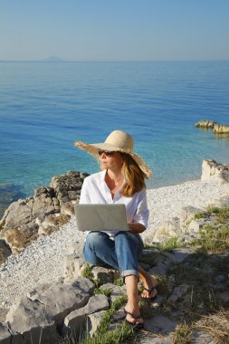 woman working with laptop on beach