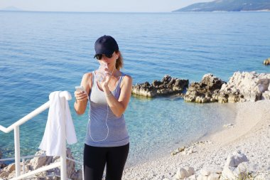 woman standing at seaside after workout