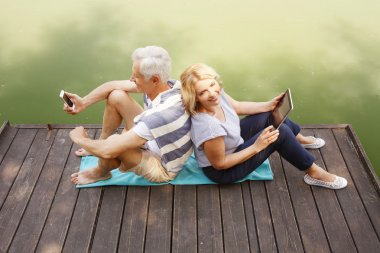 couple on pier holding tablet and phone