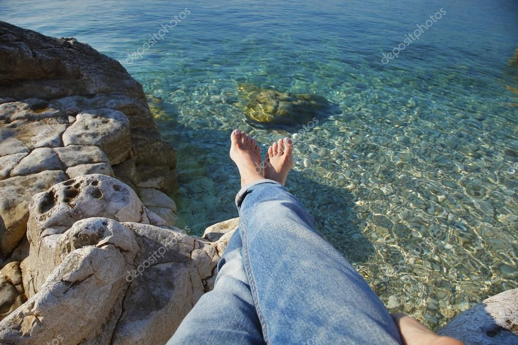 woman with bared feet relaxing at beach