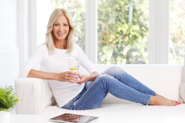 Portrait of beautiful mature woman smiling while sitting at sofa at home and drinking a glass of water. stock vector