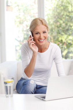 Portrait of middle age woman sitting at home in front of laptop while working on laptop and making call. stock vector