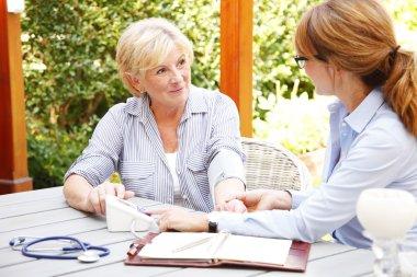 Elderly woman with nurse using blood pressure