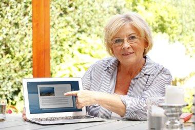 woman in garden in front of laptop