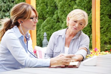 Home caregiver female consulting with patient