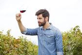 Fotografie vinař, drží v ruce skleničku