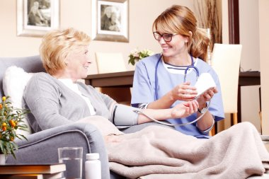 woman sitting at home while nurse