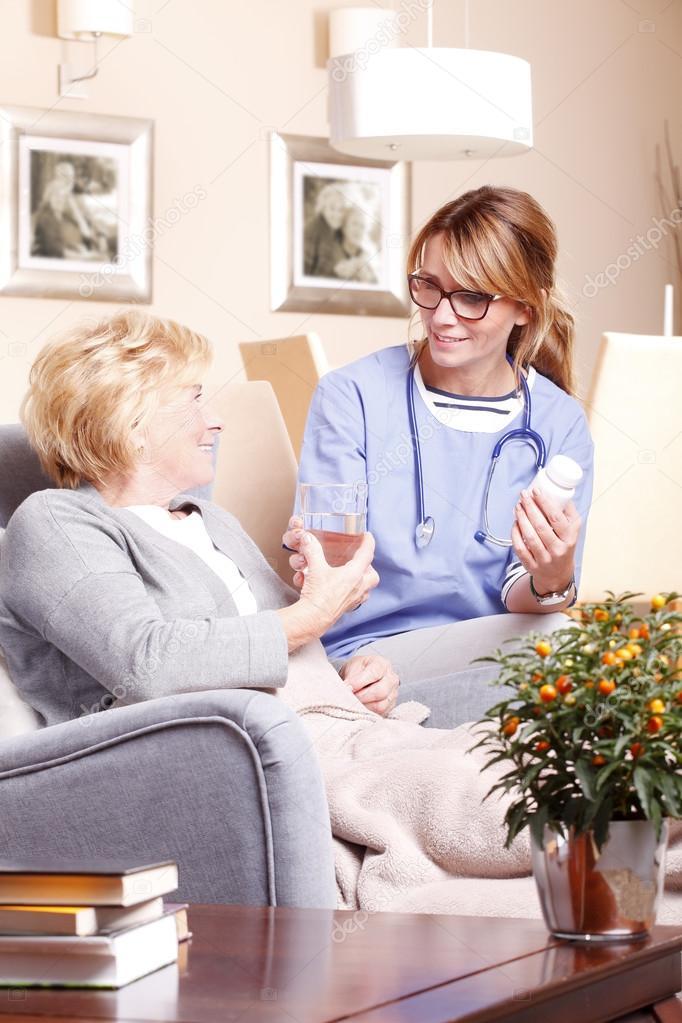 nurse giving medication to  woman.