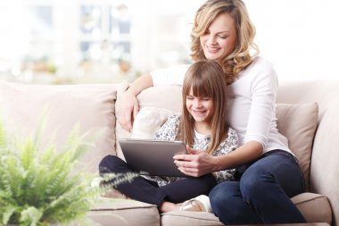 mother and  daughter using  digital tablet.