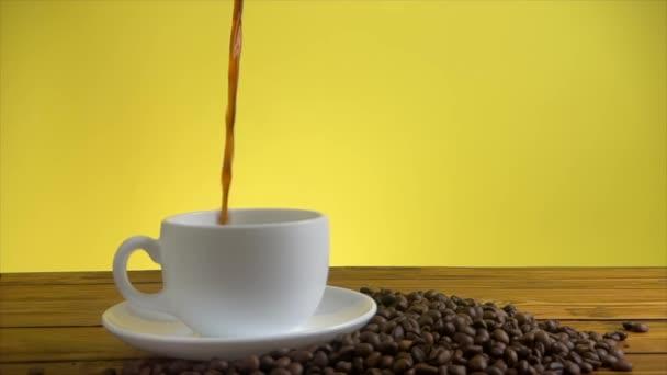 Nalévání kávy z turecké konvice na kávu v bílém šálku