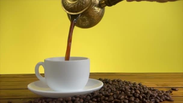 Kávé öntése török kávéskancsóból fehér pohárban