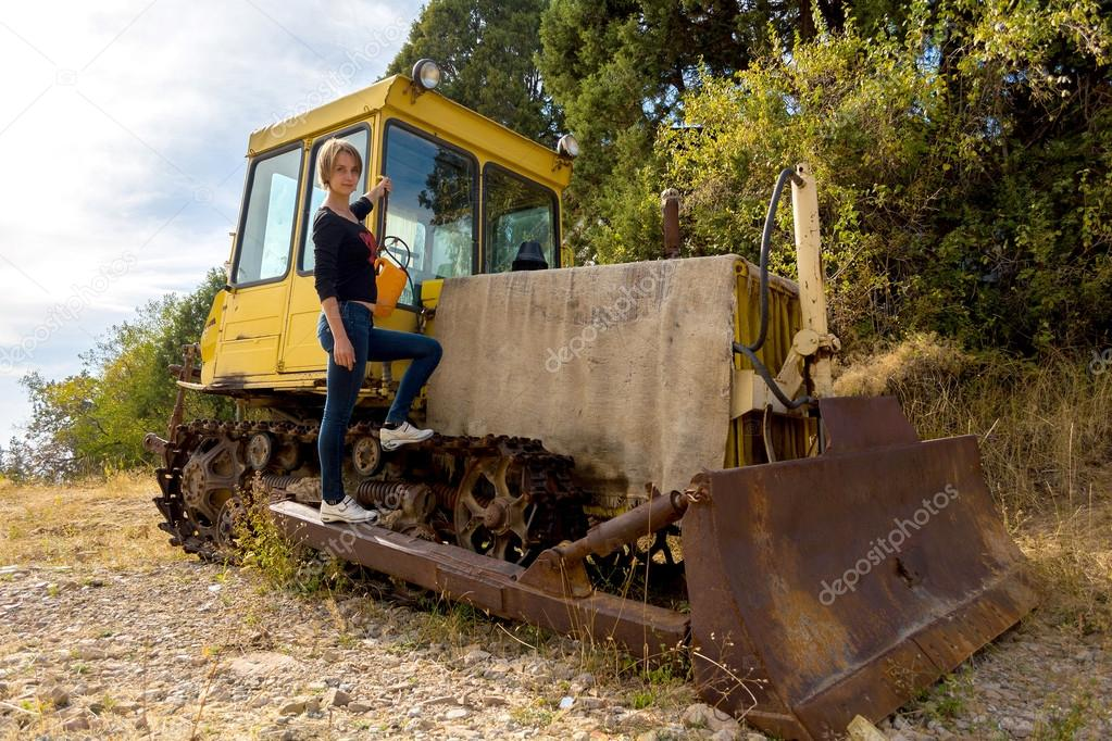 Young girl with old bulldozer