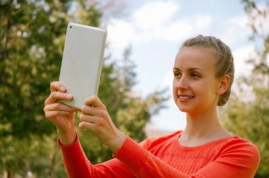 Young woman making selfie with tablet in green park