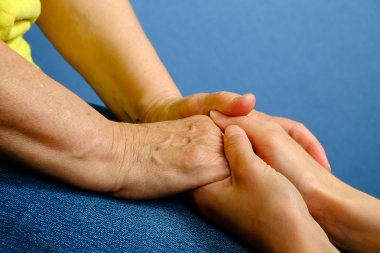 Hands of young woman holding hands of an elderly woman